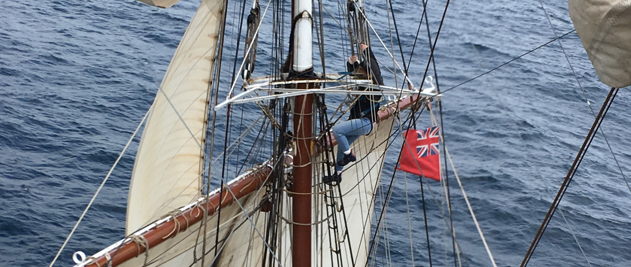 Trainee climbing the mast on the Tall Ship Morgenster