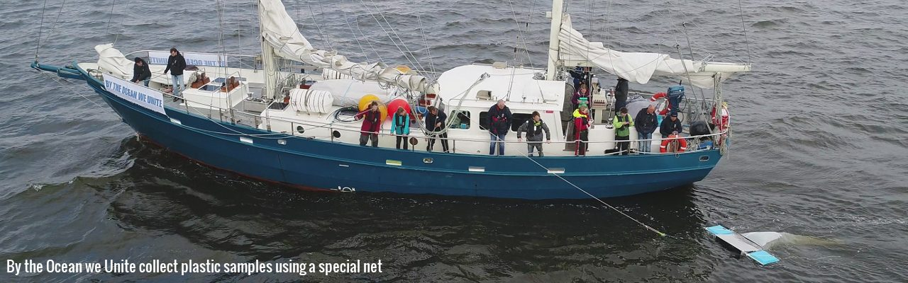 Picture of people on a sailing boat collecting plastic samples from the sea